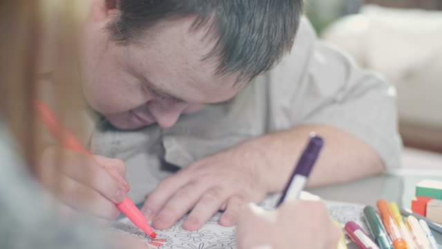 man with development disability enjoying coloring - disability stock videos and b-roll footage