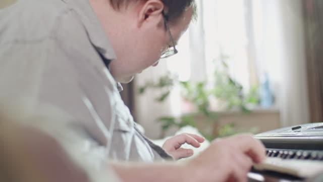 vídeos y material grabado en eventos de stock de man with development disability playing piano - instrumento musical