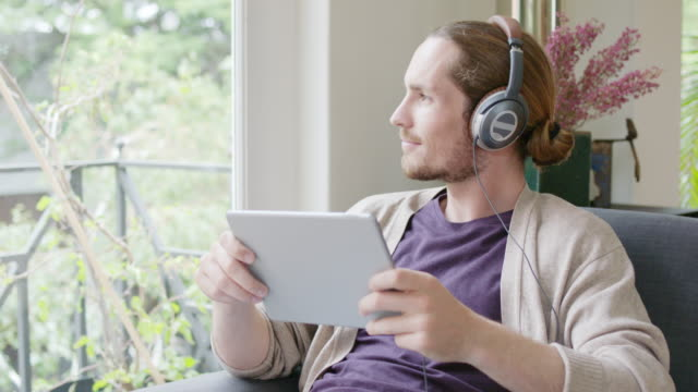 Man with digital tablet listening music at home