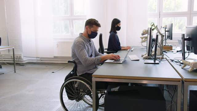 vídeos de stock e filmes b-roll de man with disability working in office post pandemic - accessibility