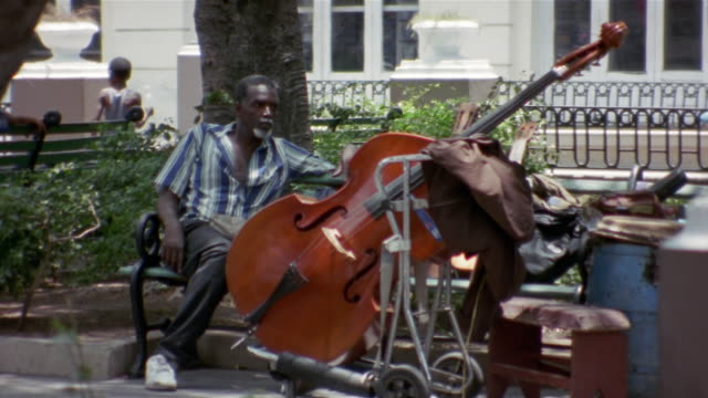 MS, Man with double bass sitting on bench in park, Santiago de Cuba, Cuba
