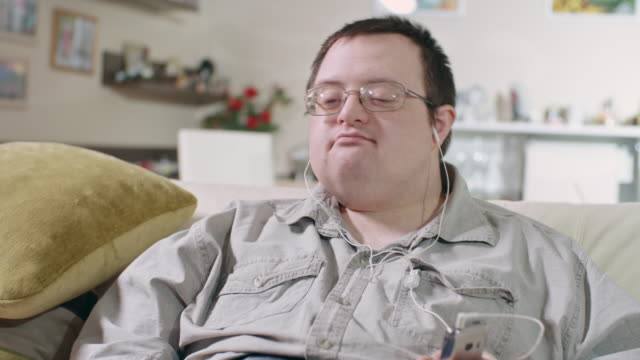 man with down syndrome listening to music in living room - nodding head to music stock videos and b-roll footage