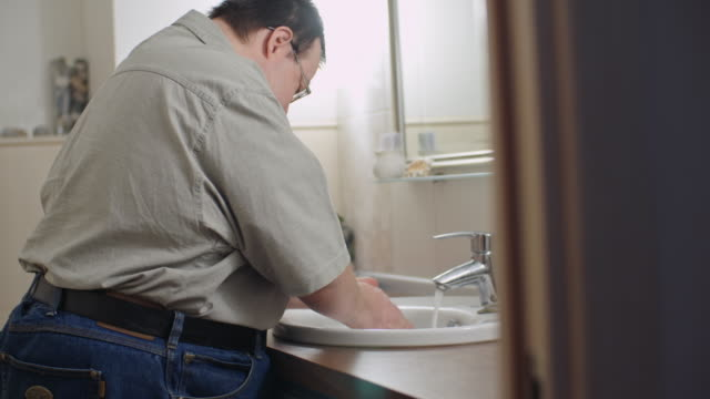 Man with Down syndrome washing hands in bathroom