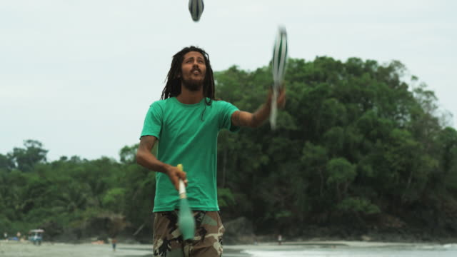 man with dreadlocks and a beard juggling on the beach - jonglieren stock-videos und b-roll-filmmaterial