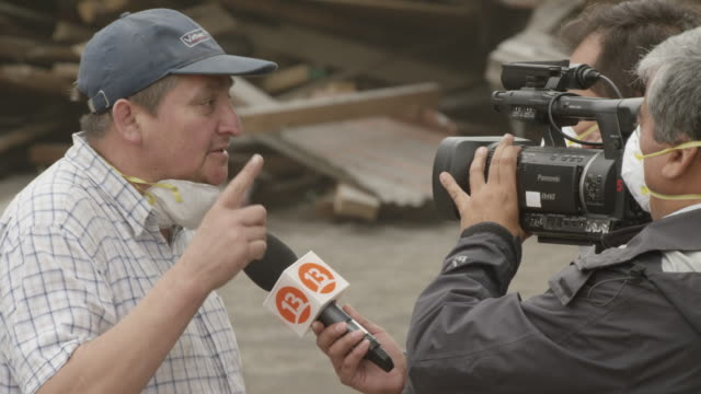 ensenada, chile - april 26, 2015: man with dust mask being interviewed by camera crew - south america stock videos & royalty-free footage