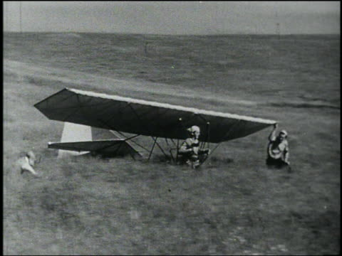 b/w man with early hang glider running in field wipes out - 発明家点の映像素材/bロール