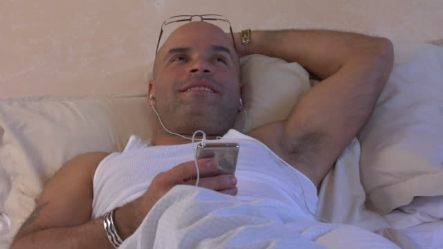 CU, ZO, MS, Man with earphones listening mp 3 player in bed