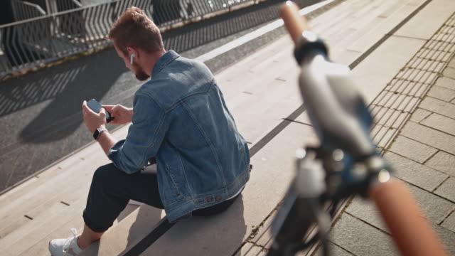 man med hörlurar med telefon med elektrisk skoter - endast en ung man bildbanksvideor och videomaterial från bakom kulisserna