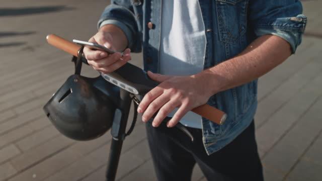 uomo con scooter push elettrico con cellulare - young men video stock e b–roll