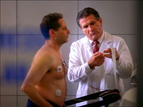 vídeos y material grabado en eventos de stock de man with electrodes walking on treadmill in stress lab as middle-aged doctor examines printout - latido cardíaco