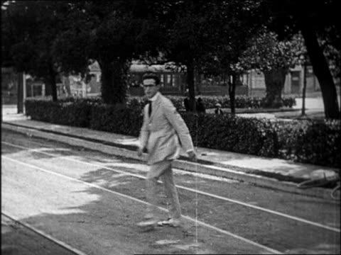 vídeos y material grabado en eventos de stock de b/w 1920 man with eyeglasses crossing street / feature - sólo hombres jóvenes