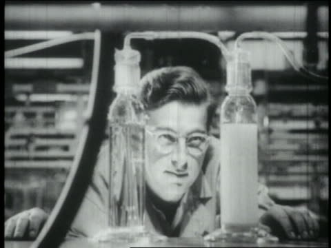 B/W 1965 man with eyeglasses looking at tubes in scientific lab