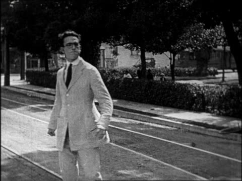 vídeos de stock e filmes b-roll de b/w 1920 man with eyeglasses standing determined in middle of street / feature - só homens jovens