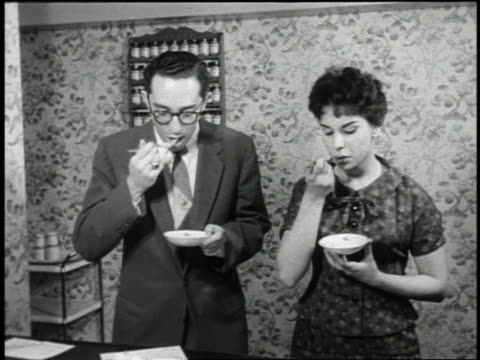 b/w 1959 man with eyeglasses + woman wearing dress sampling food for home taste test - conformity stock videos & royalty-free footage
