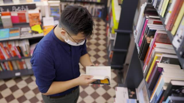 vídeos y material grabado en eventos de stock de hombre con máscara facial en la librería eligiendo un libro para comprar - gafas