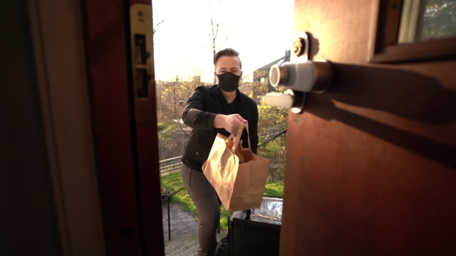 vídeos de stock e filmes b-roll de man with face mask delivering food - serviços essenciais