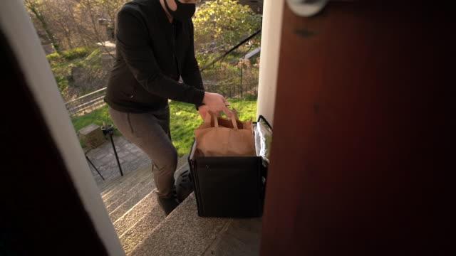 mann mit gesichtsmaske liefert nahrung - liefern stock-videos und b-roll-filmmaterial
