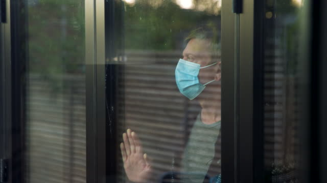 man with face mask looking through window - obscured face stock videos & royalty-free footage