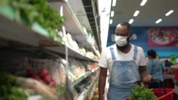 Man with face mask walking and shopping in supermarket