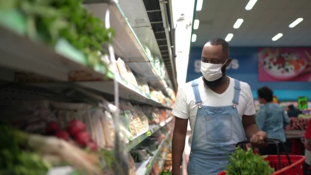 man with face mask walking and shopping in supermarket - groceries stock videos & royalty-free footage