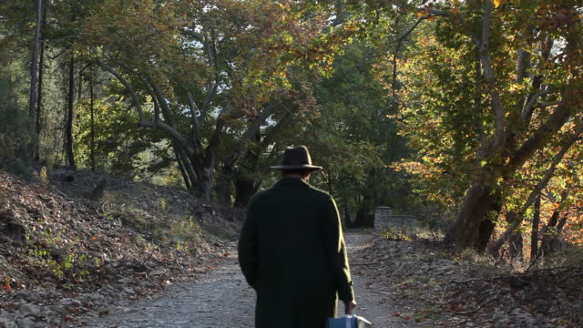 Man with fedora and coat walking in autumn atmosphere