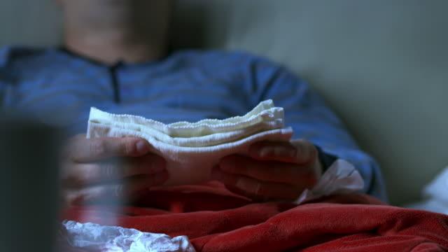 hd: mann mit fieber putting-bandage auf seiner stirn - schlafanzug stock-videos und b-roll-filmmaterial