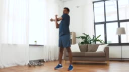 man with fitness tracker stretching body at home