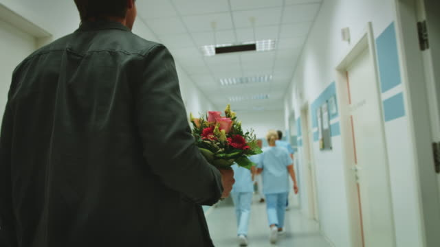 man with flower bouquet walking in clinic corridor - visit stock videos & royalty-free footage