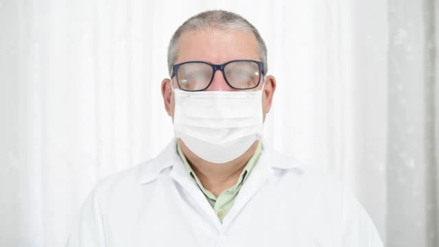 man with fogging glasses because of wearing protective mask and smiling after that - eyeglasses stock videos & royalty-free footage