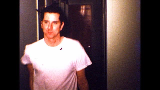 man with gelled hair struts down a hallway and makes a kissy-face at the camera. - rynka ihop ansiktet bildbanksvideor och videomaterial från bakom kulisserna
