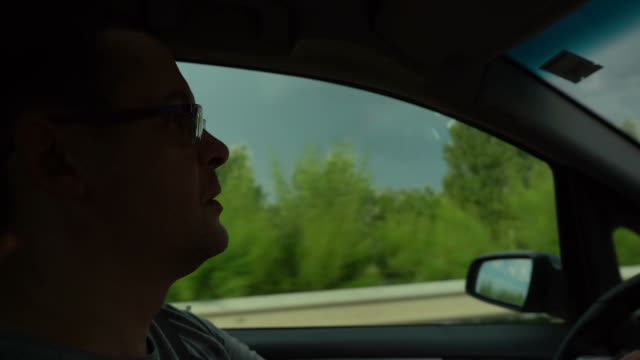 man with glasses driving a car on a highway - ethnicity stock videos & royalty-free footage
