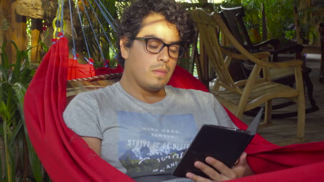 Man with glasses in a hammock reading an e-book. Located in a porch in a tropical country. Cabin Retreat - Brief