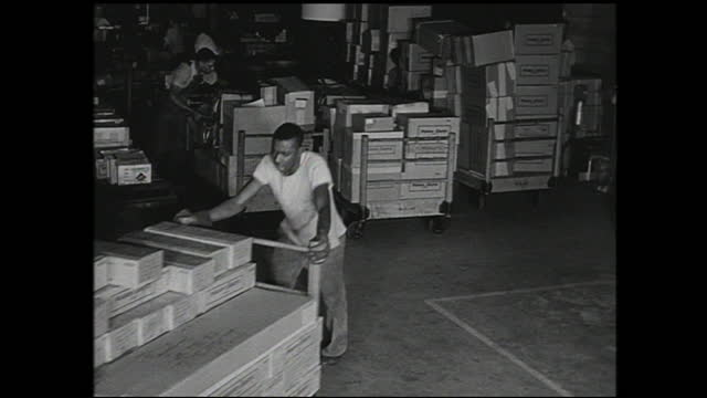 "man with glasses looking at paperwork; finger pointing at ""national defense project"" stamp on paper; boxes traveling down the conveyor belt; workers... - 1940 1949 video stock e b–roll"