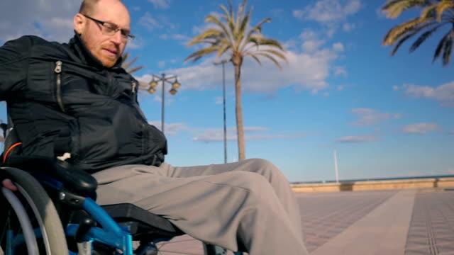 vídeos de stock e filmes b-roll de man with glasses moving wheelchair near beach - stock video - paralisia