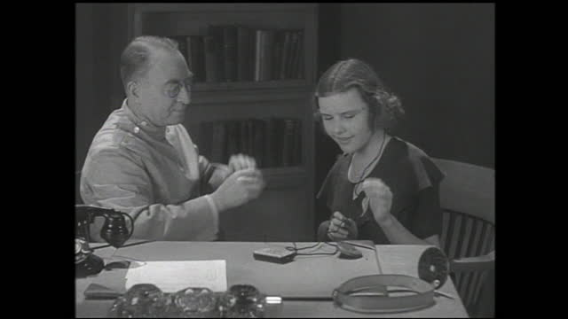 man with glasses showing girl small model and putting it in her ear behind office desk; bookcase in the background as the two talks - 1940 1949 bildbanksvideor och videomaterial från bakom kulisserna