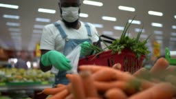 Man with gloves putting carrots on plastic bag at supermarket