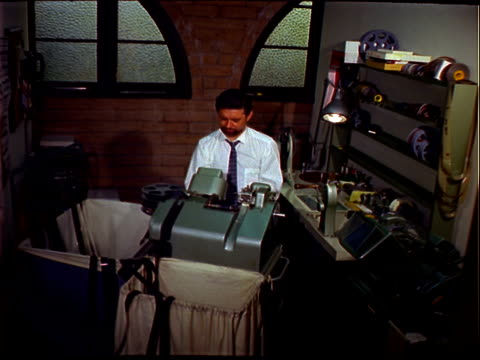 man with goatee white dress shirt and gray tie editing 35mm film on moviola upright editing machine in editing room / man loads film into machine... - film editing stock videos & royalty-free footage