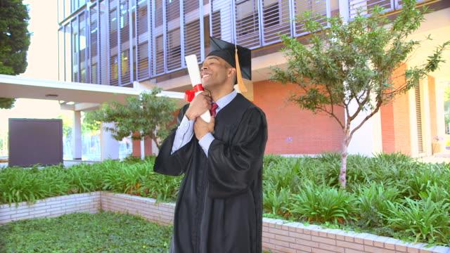 vídeos de stock e filmes b-roll de  man with graduation gown and diploma - fotografia de três quartos