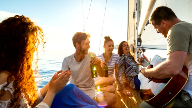 man with guitar and friends on sailboat - 20 29 years stock videos & royalty-free footage