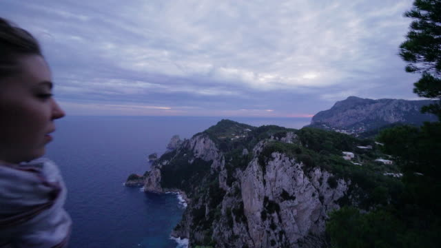 man with hair bun admires the view of the coast of capri in italy on cloudy day - mid length hair stock videos & royalty-free footage