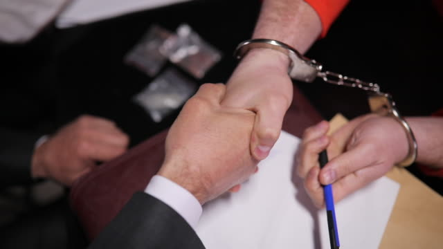 man with handcuffs shaking hand with lawyer in interrogation room - probation stock videos & royalty-free footage