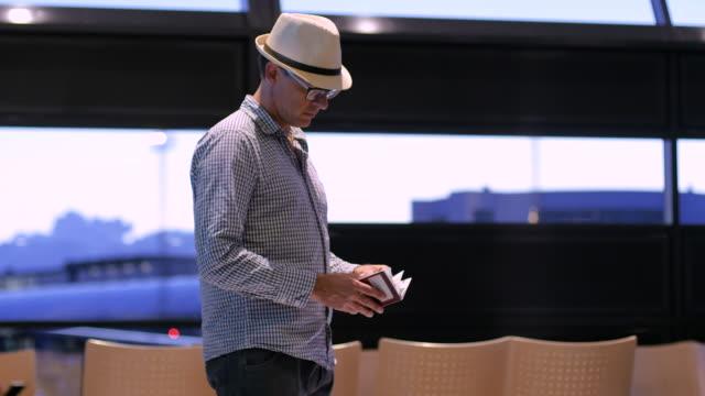man med hatt och glasögon som tittar på pass och biljett vid flygplatskontroll giltighet - visa bildbanksvideor och videomaterial från bakom kulisserna