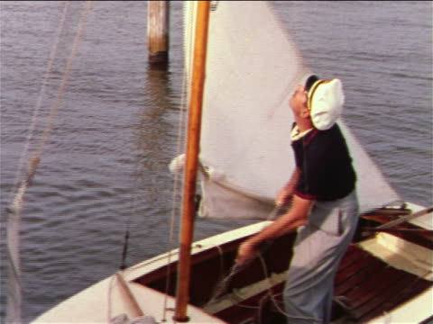 1959 man with hat raising sail on small sailboat in water / industrial - 1959 stock videos & royalty-free footage