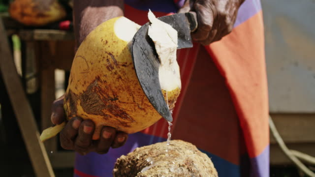 ms man with hatchet cutting fresh yellow coconut,sri lanka - sri lanka stock videos & royalty-free footage