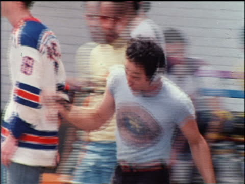 vidéos et rushes de 1978 man with headphone radio on roller skates dancing in busy nyc park / educational - 1978