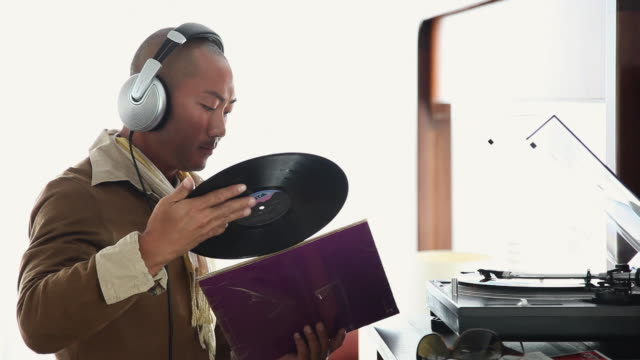 cu ts man with headphones standing by record player putting record back in sleeve / palma de mallorca, mallorca, baleares, spain - sleeve stock videos and b-roll footage