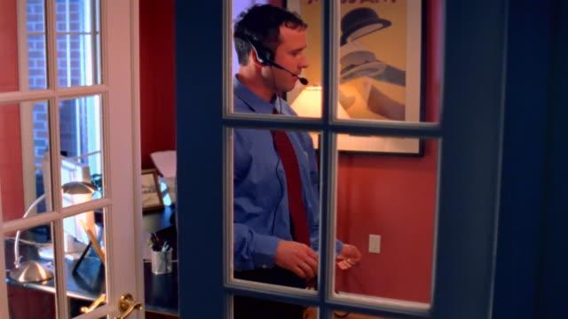 stockvideo's en b-roll-footage met man with headset in home office - tuindeur