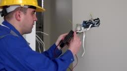 Man with helmet testing socket with voltmeter