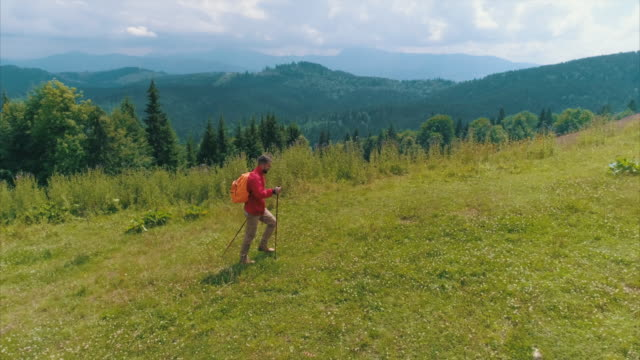 man with hiking poles exploring view in mountains - hiking pole stock videos and b-roll footage