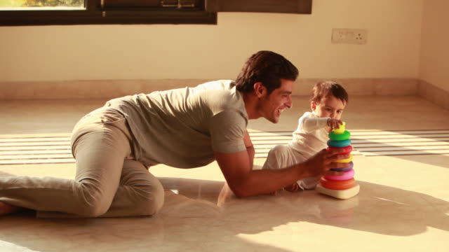 man with his son playing with a plastic toy  - flooring stock videos & royalty-free footage